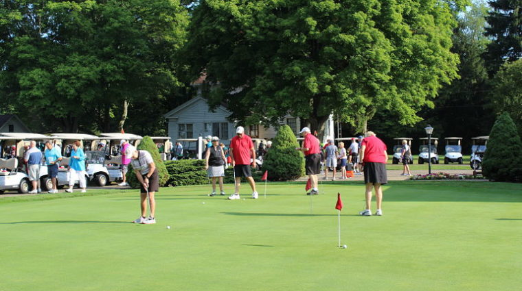 YWCA Carnation Scramble golfers practice putting